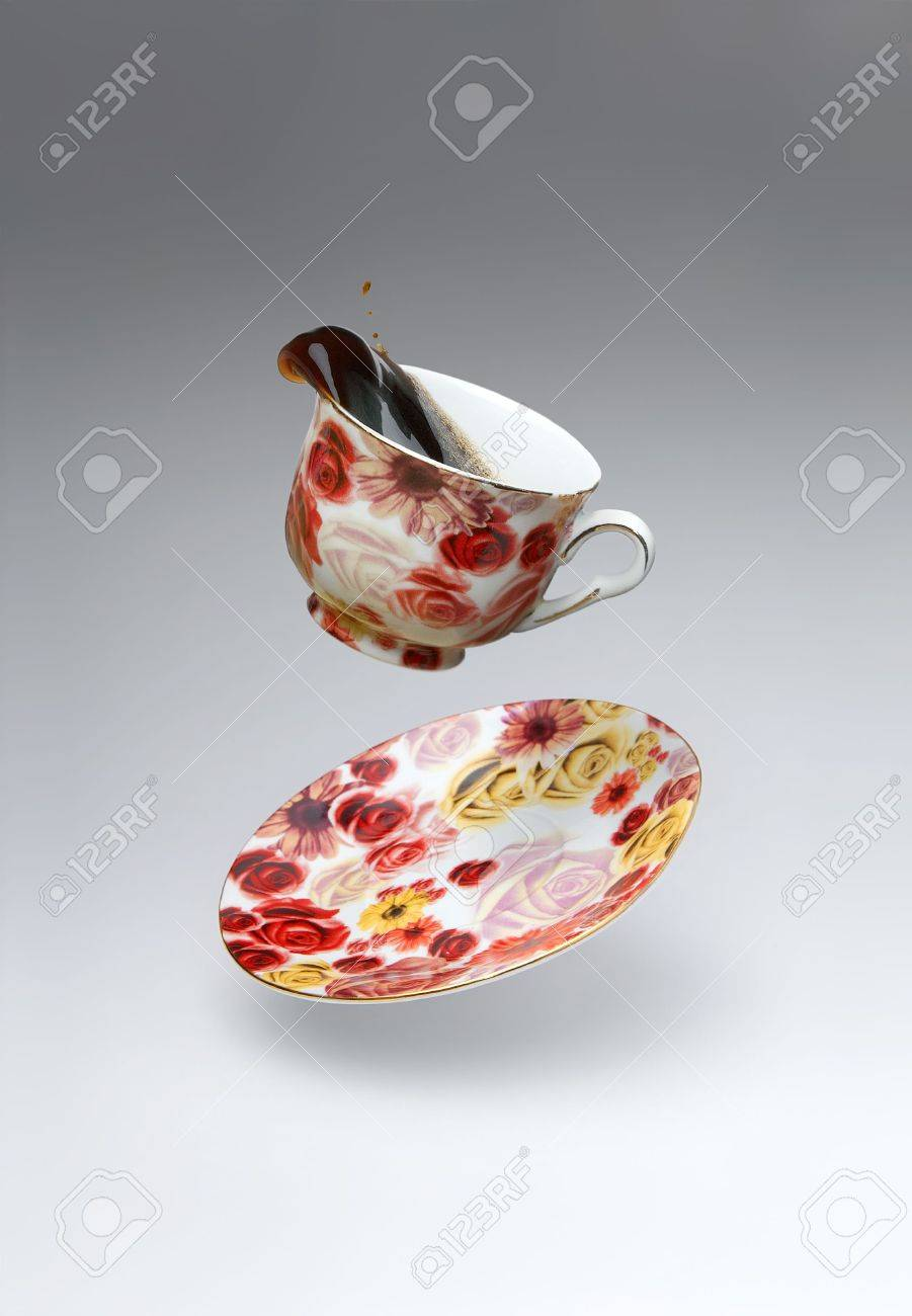 Colored plate and cup of coffee on grayscale background in motion Stock Photo - 3337374
