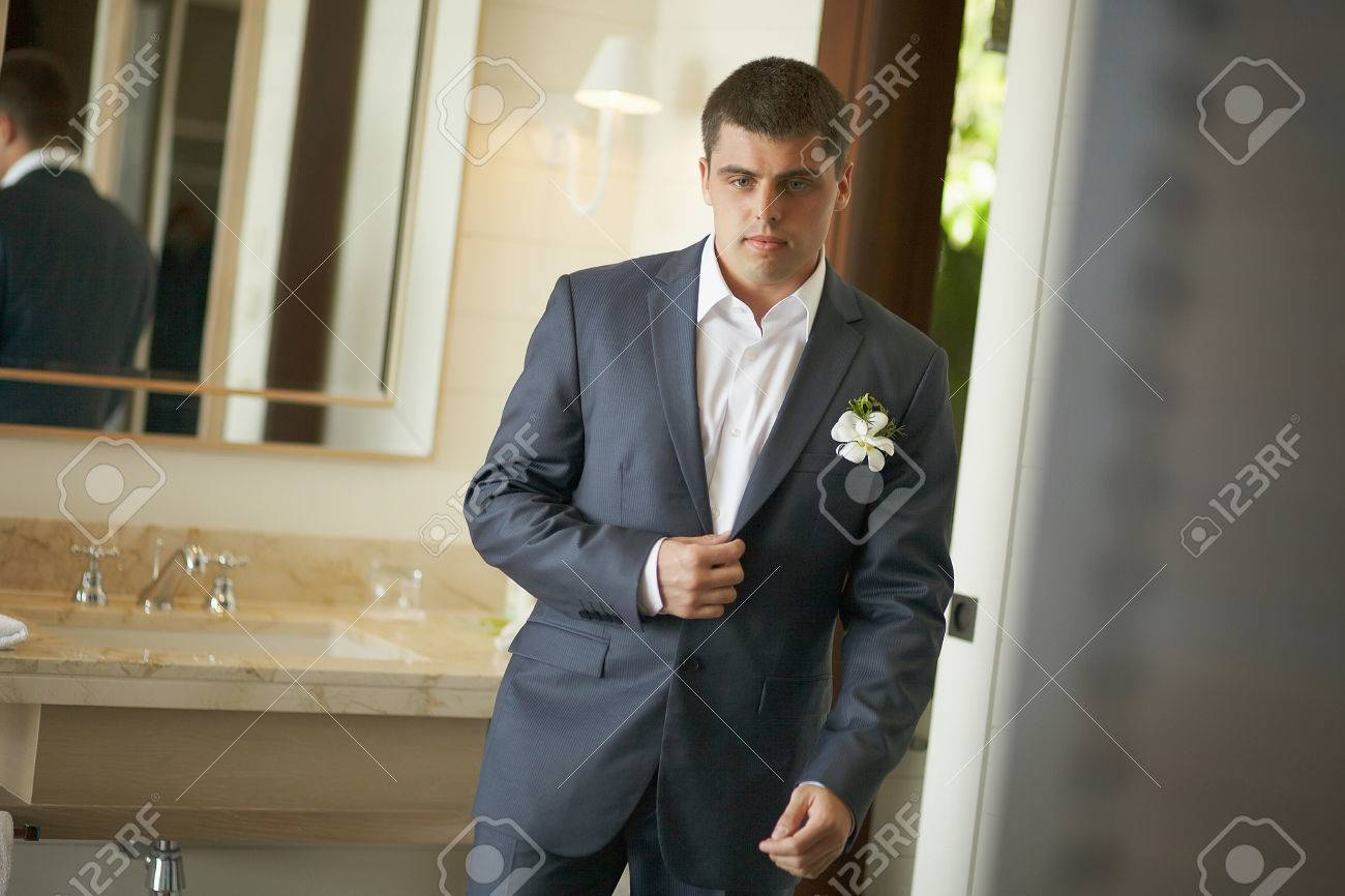Handsome And Strong Man Putting On Official Suit. Nice And Slender ...