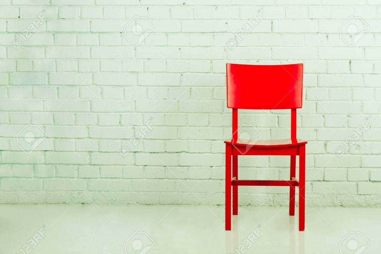 Empty chair in room - Red Chair In Empty Room Against A Brick Wall With Copy Space Stock Photo