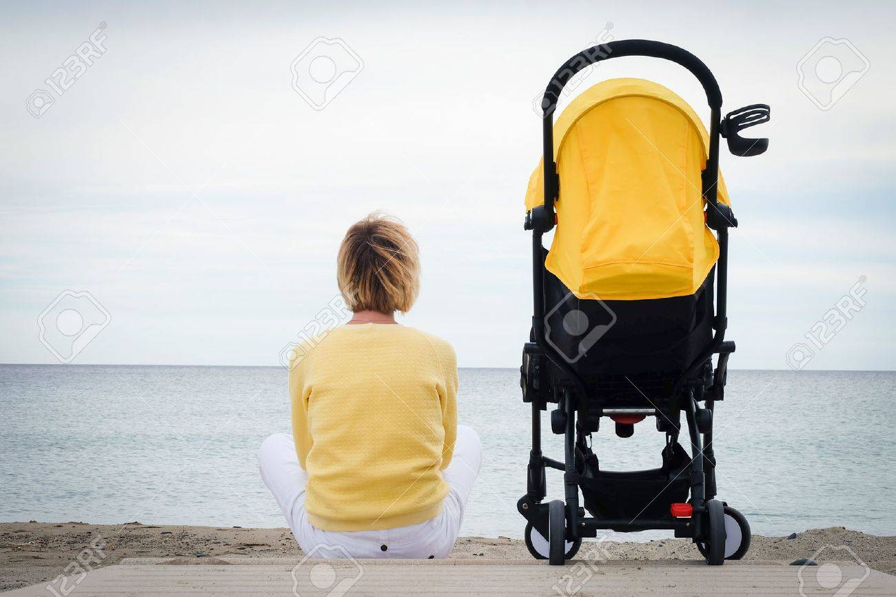 Woman looking through the sea while sitting on beach with baby carriage. Young mother sitting outdoor with stroller. Maternity concept with copyspace - 71856557