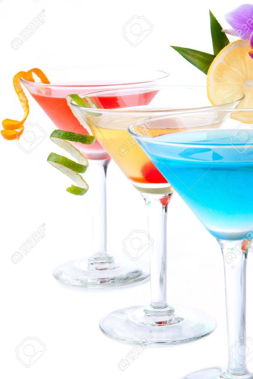 Summer Tropical Martini Cocktails with vodka, apple and peach liqueur, pineapple and cranberry juice, lime, lemon, blue curacao, maraschino cherry, and orchid isolated on a white background Stock Photo - 8373262