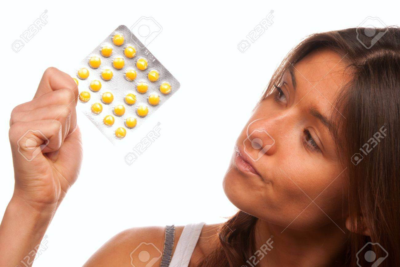 Pretty young woman looking at full medicine pack of yellow tablet pills thinking about doctor's prescription to take one or not isolated on a white background Stock Photo - 8486559