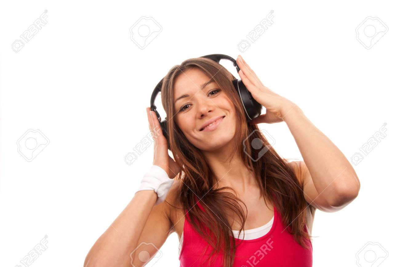 Attractive fitness brunette woman listening and enjoyingmusic in headphones, smiling, laughing and looking in camera isolated on a white background Stock Photo - 8703489