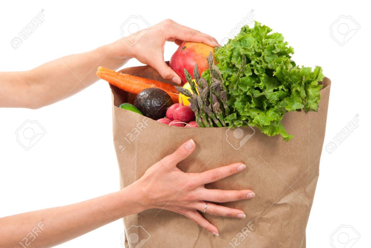 Hands holding a shopping paper bag full of groceries, one hand pick out ripe mango, avocado, asparagus, carrots, radish, lime and lemon on a white background Stock Photo - 9057263