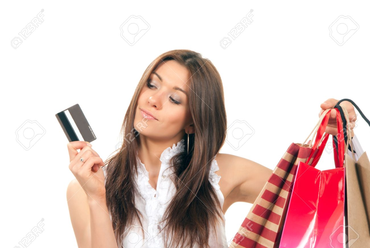 Pretty beautiful girl holding gift credit card in one hand and shopping bags presents in another on a white background. Stock Photo - 9137805