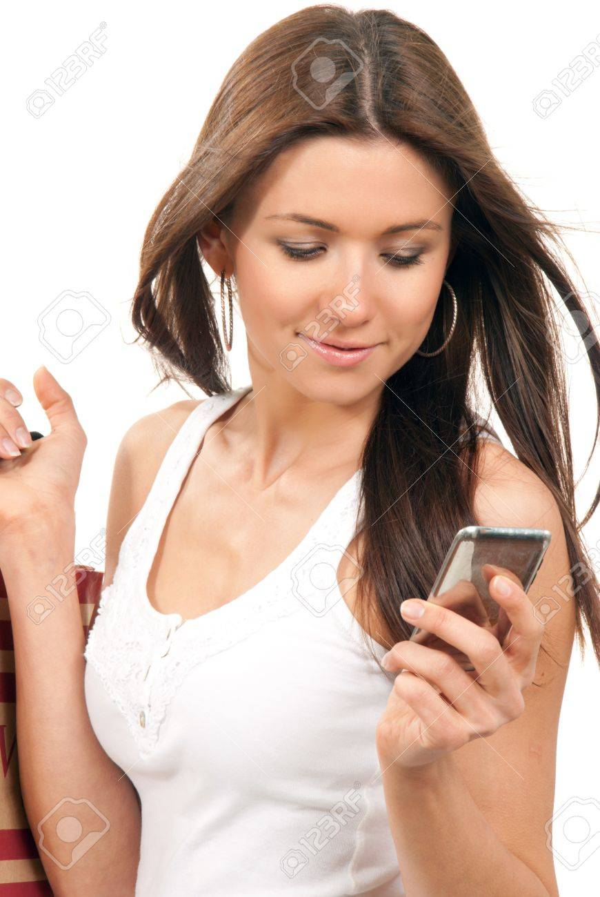 Pretty smiling girl reading texting a message on the cellphone mobile and holding shopping bags in hands on a white background Stock Photo - 9168006