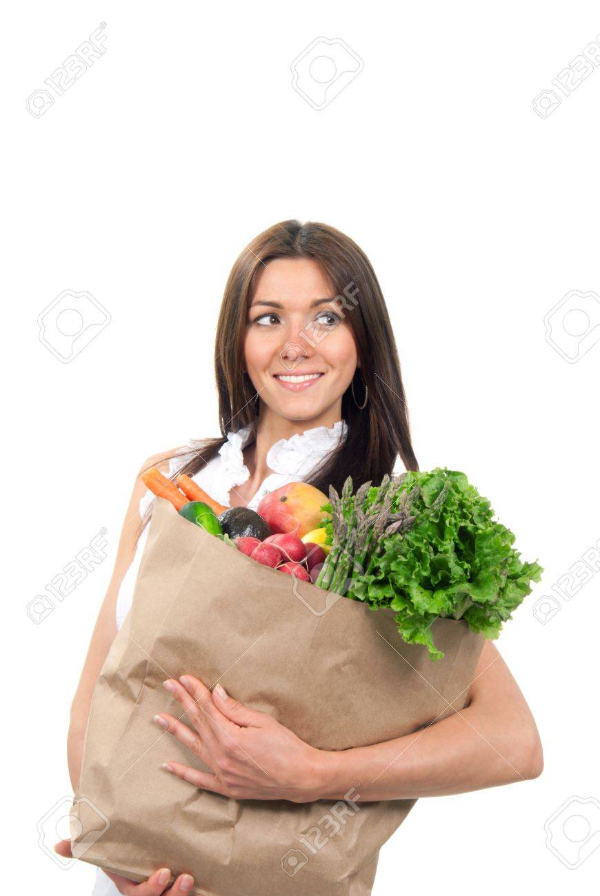 Pretty woman mother smiling and holding supermarket shopping paper bags full of vegetables: mango, asparagus, lettuce, radish, carrot in her hands on a white background Stock Photo - 9424670