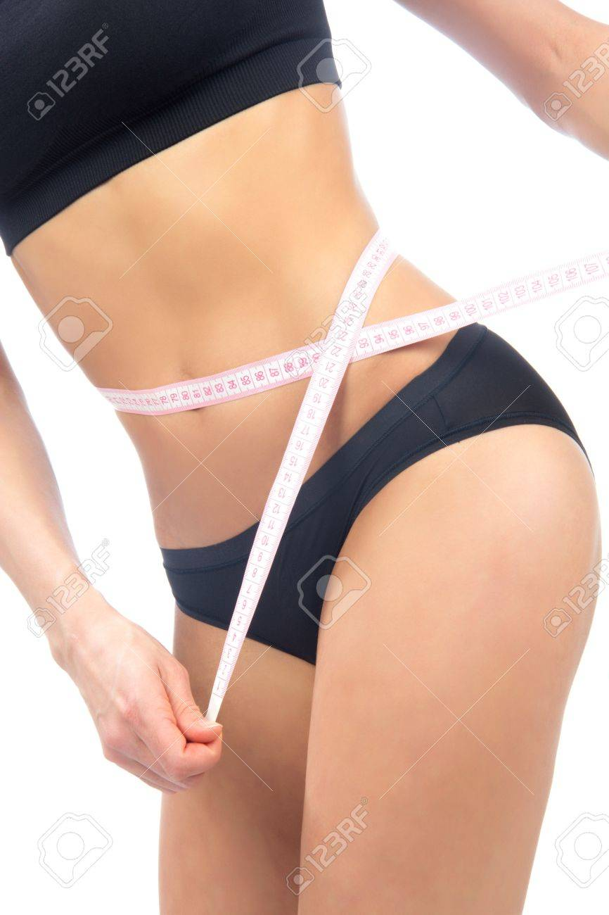 Athletic fit slim woman measuring her waist metric tape measure after a diet isolated over white background Stock Photo - 12769875