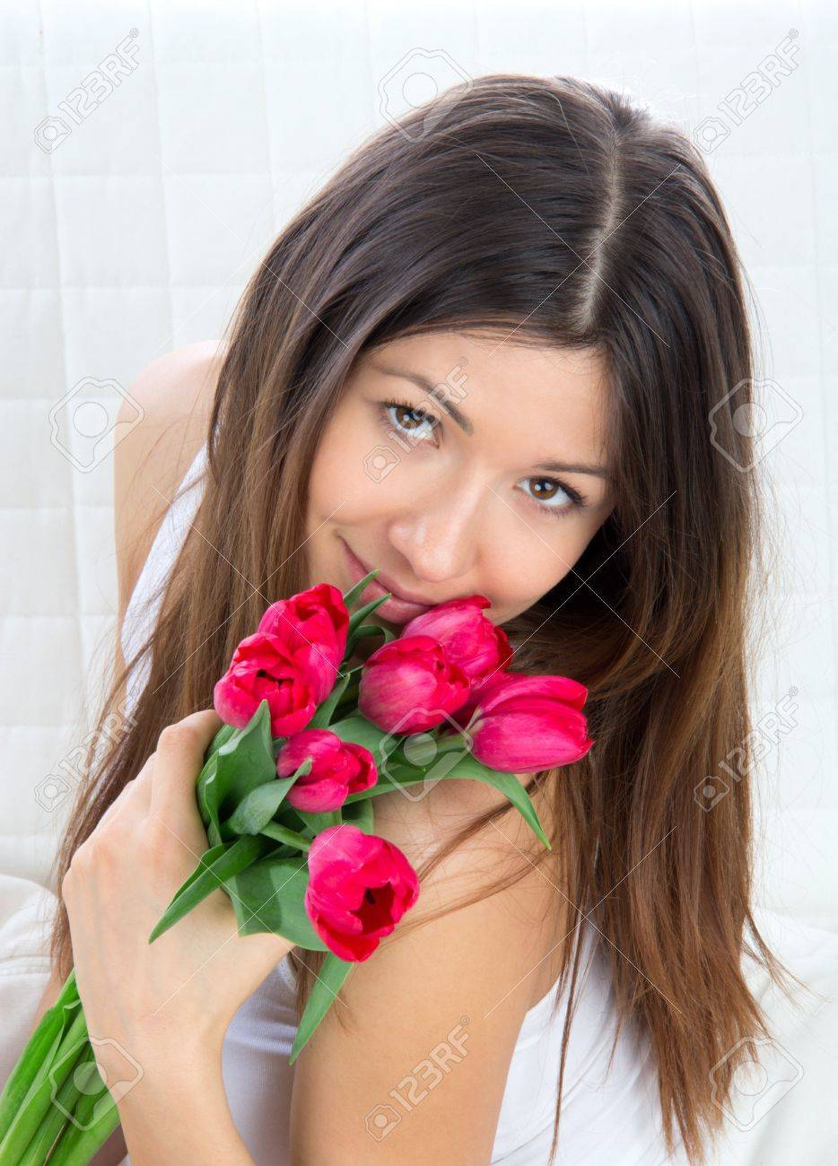 Beautiful young woman with bouquet of red tulips flowers sitting on couch, smiling Stock Photo - 12770445