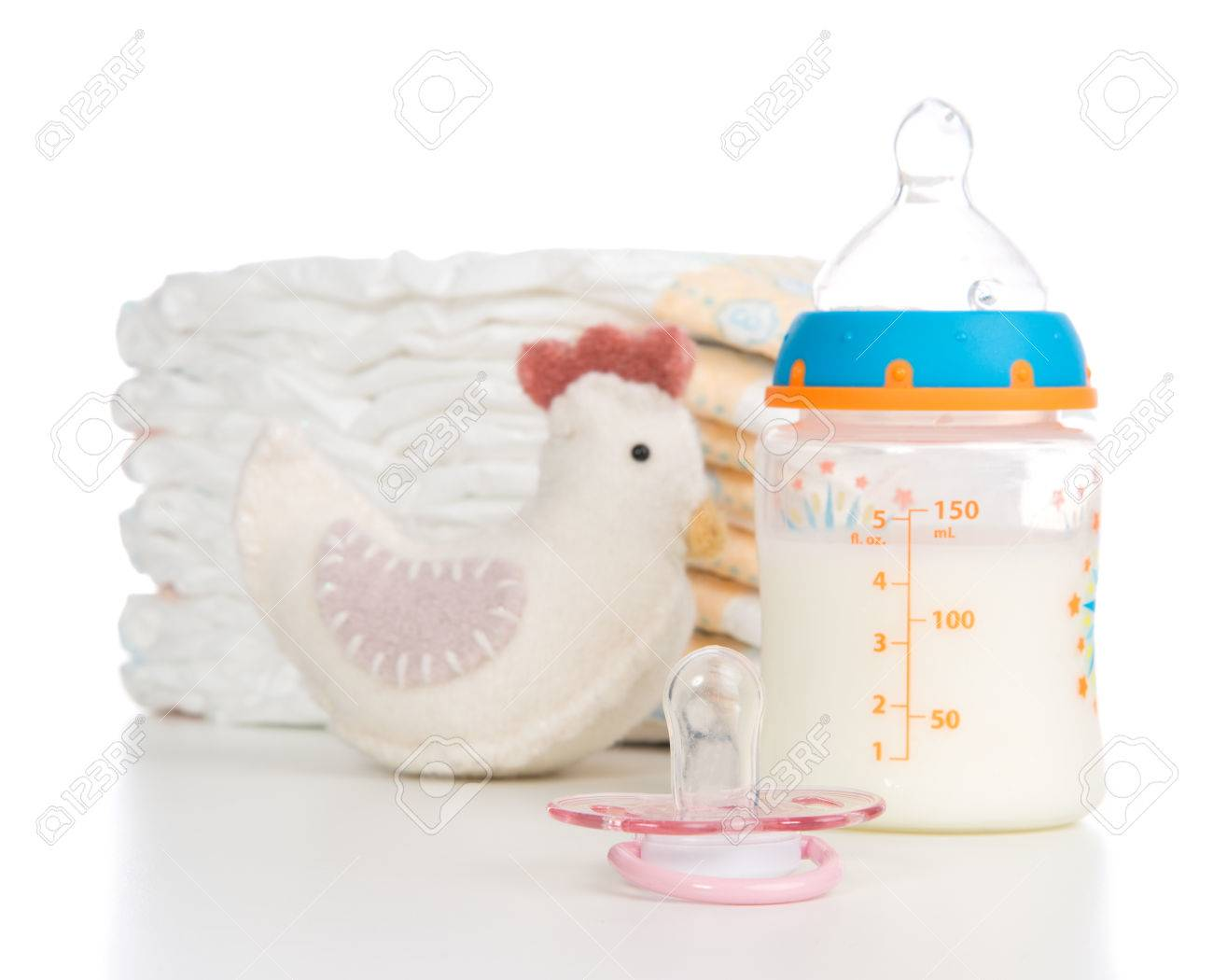 Child stack of diapers, nipple soother, toy and baby feeding bottle with milk on a white background Stock Photo - 25370651
