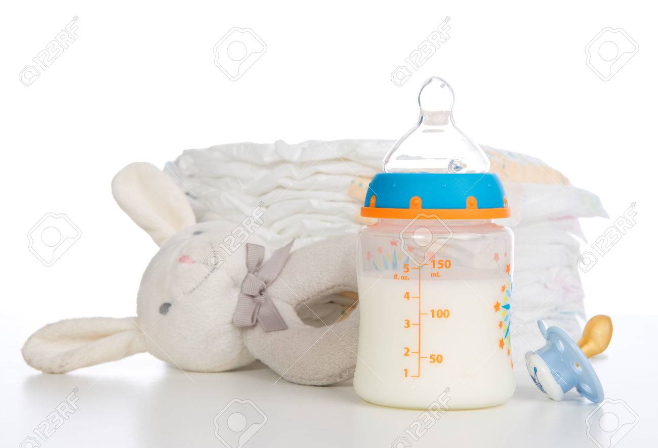 New born child stack of diapers, nipple soother, beanbag bunny toy and baby feeding bottle with milk on a white Stock Photo - 25749712