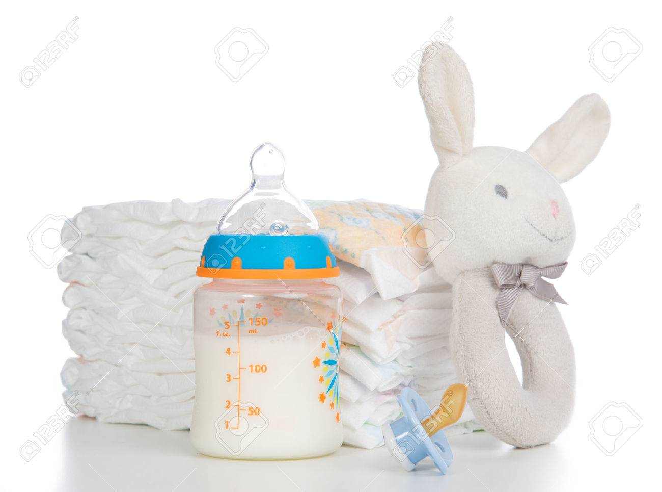 New born child stack of diapers, nipple soother, beanbag bunny toy and baby feeding bottle with milk on a white background Stock Photo - 26134317