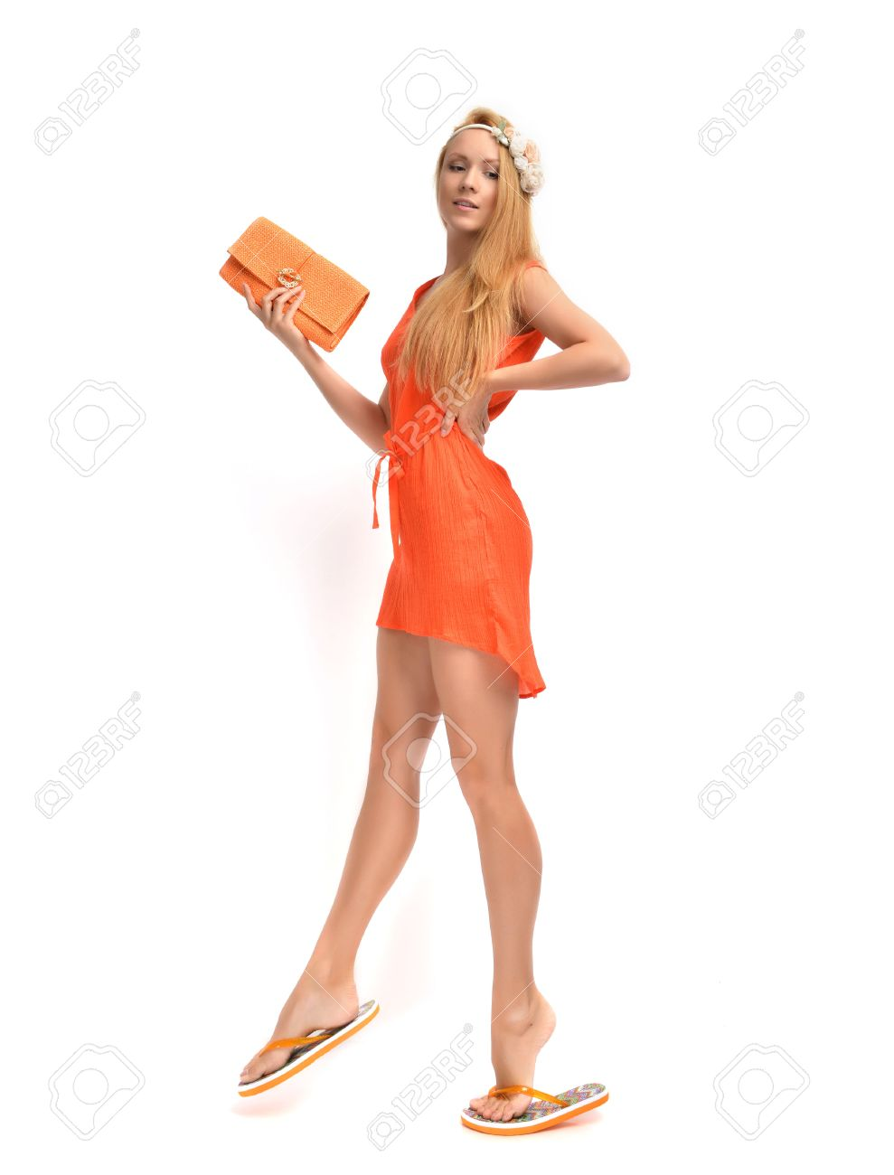 5833beb65120 Stock Photo - Young beautiful caucasian red hair woman walking in flip flops  and gorgeous orange dress with modern clutch isolated on a white background