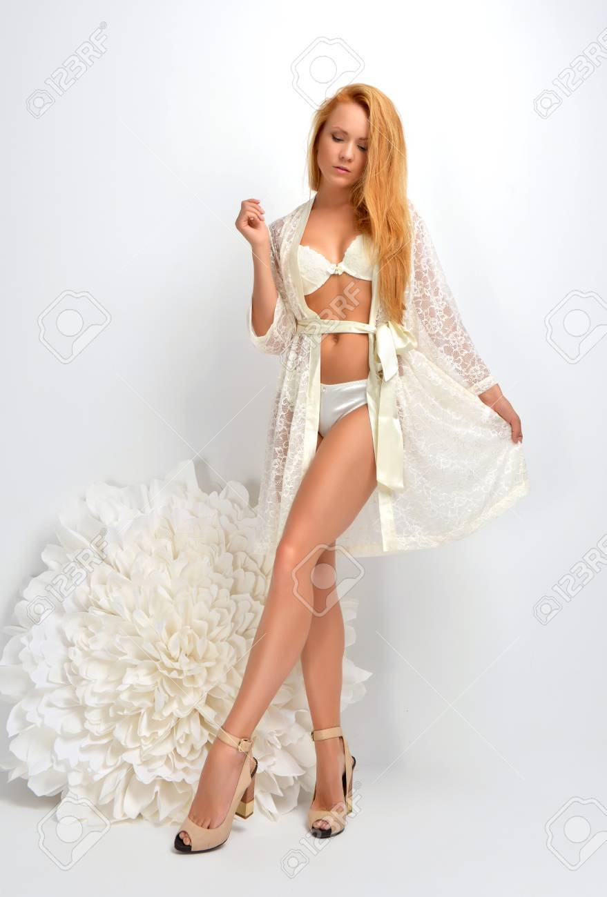 Beautiful red hair bride in white lingerie standing in her bedroom on a  white background Stock d3d364583