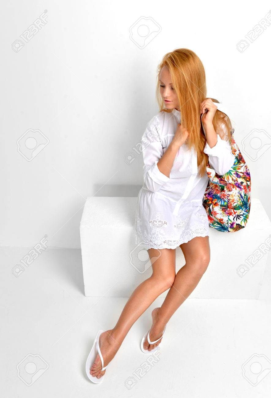 Stock Photo - Young beautiful caucasian red hair woman sitting in flip flops  and gorgeous white dress with modern bag clutch on a white background 905be907c