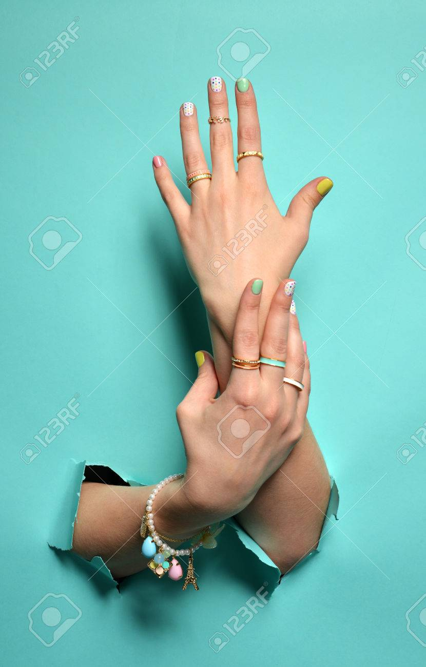 Beautiful woman hands with yellow pink white pattern nail polish and silver stacking rings and bracelets on a mint background - 52013476