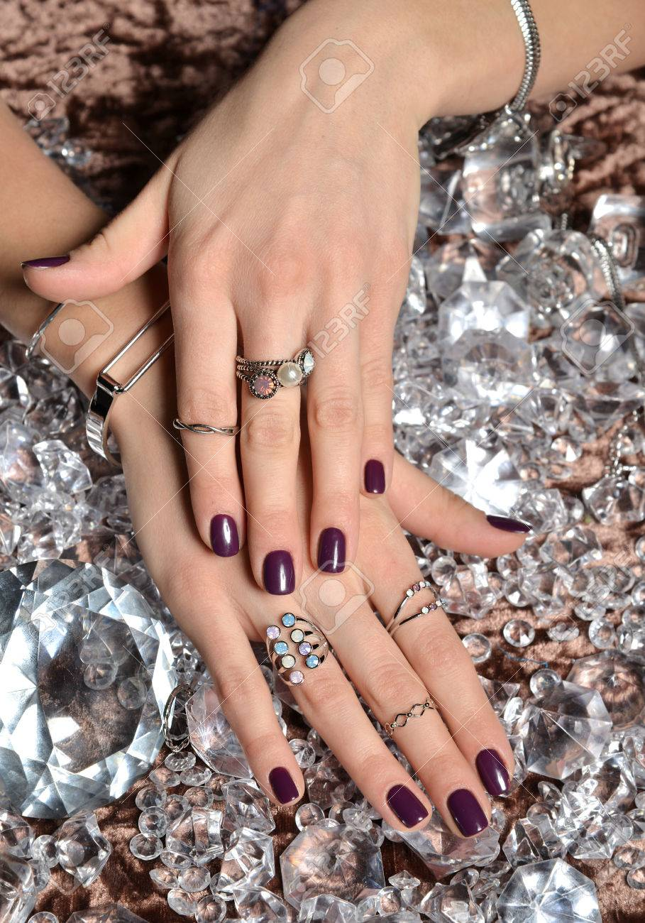 Beautiful Woman Hands With Purple Pattern Polish Nails And Silver Stacking Rings Bracelets On A