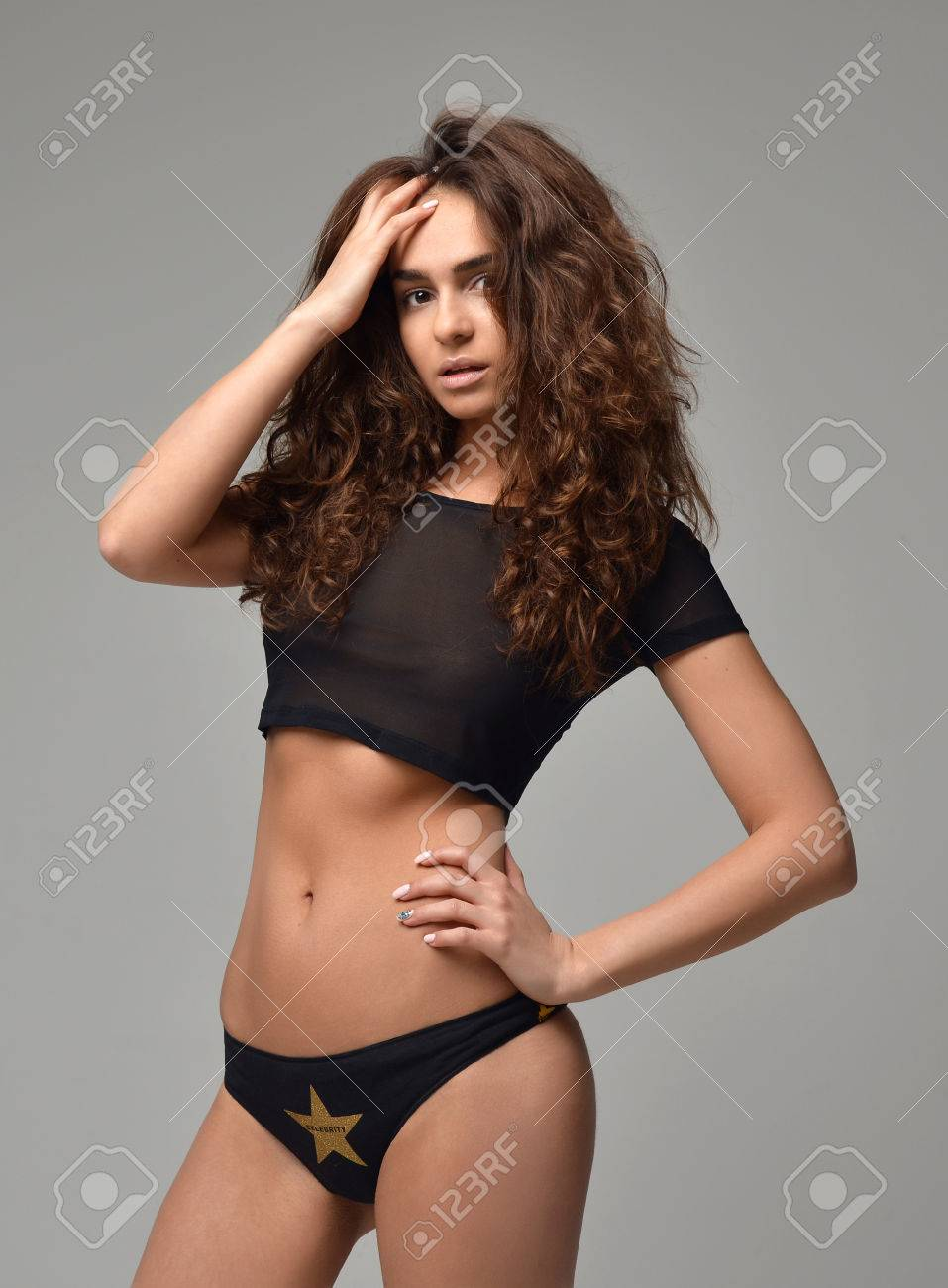 Sexy young beautiful woman posing in black modern bikini underwear vest on  a warm grey background eea8f5fbd