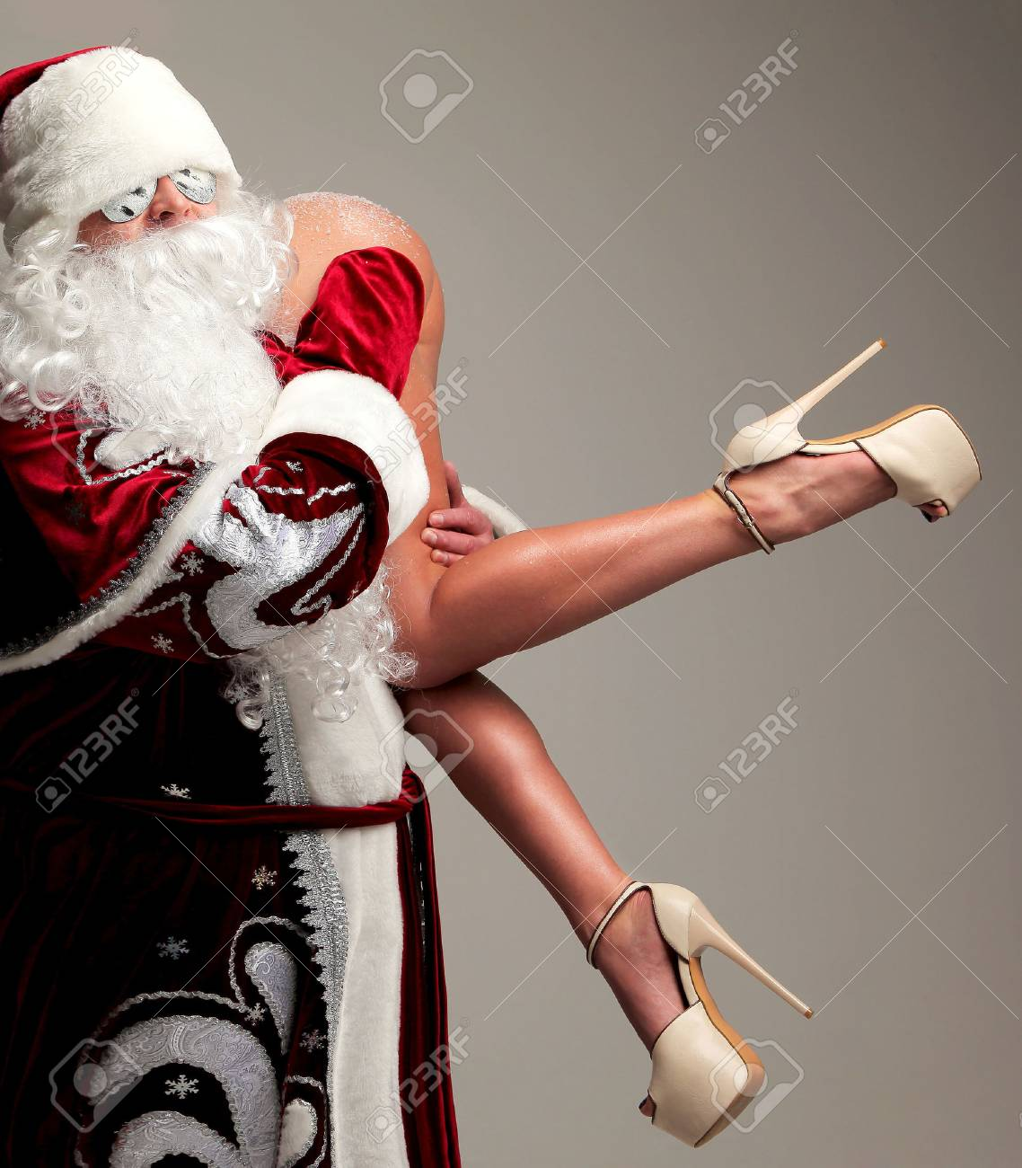 New year 2018 christmas concept. Bad santa claus in snow flakes sunglasses honding young woman with long legs and high hills - 87760920