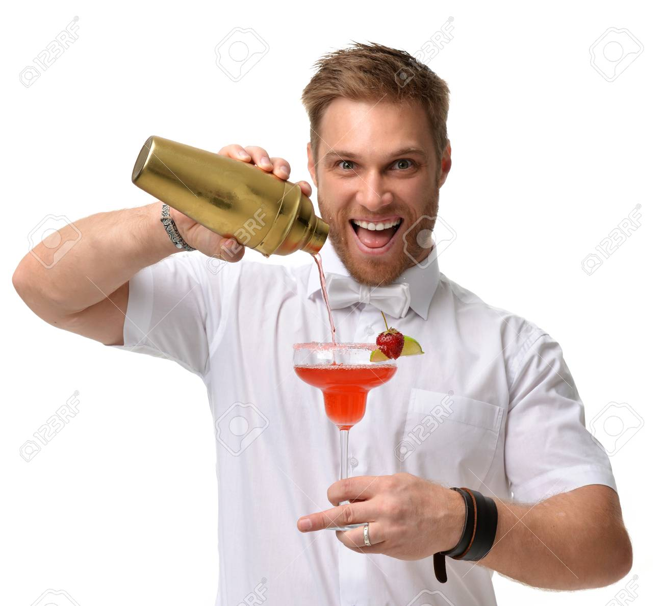 Bartender men is preparing red margarita cocktail with strawberry and lime. Hold big glass and pours alcohol from a gold shaker isolated on a white background - 88672033