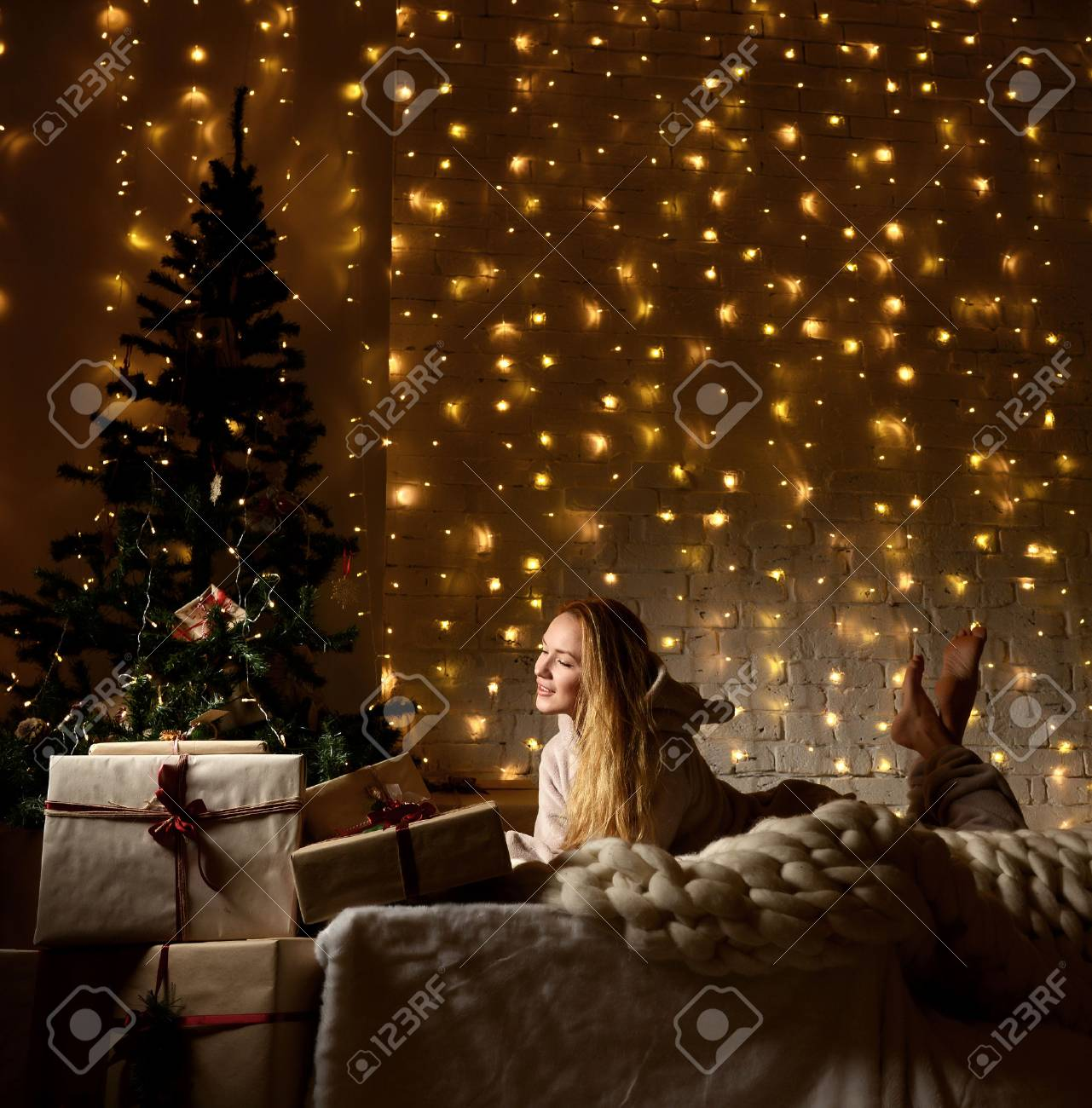 stock photo young woman lying dreaming near magical new year gifts by a christmas tree in cozy living room in winter on yellow magic light background