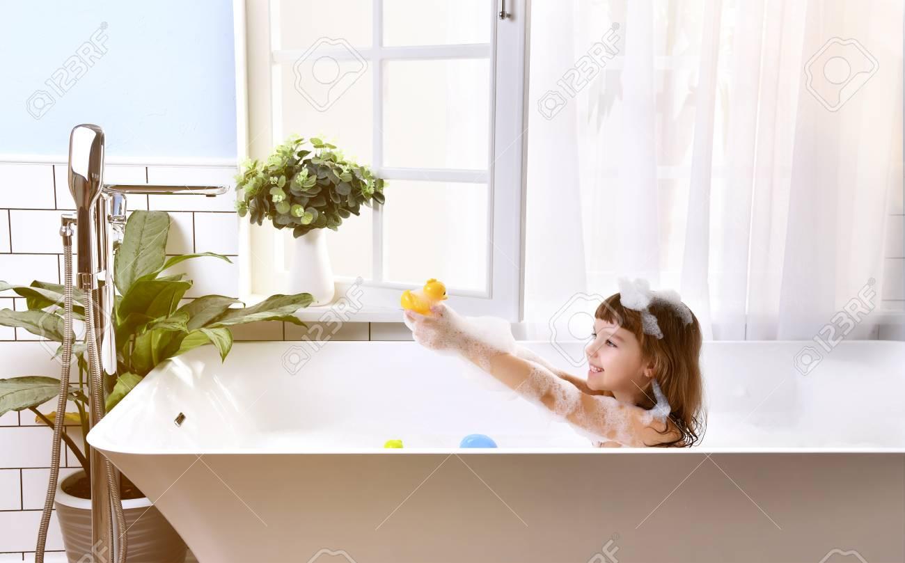 Happy little baby girl sitting in bath tub in the bathroom. Portrait of baby bathing in a bath full of foam near window - 93788020