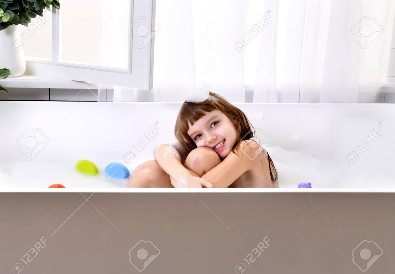 Happy Little Baby Girl Sitting In Bath Tub Playing With Yellow Duck ...