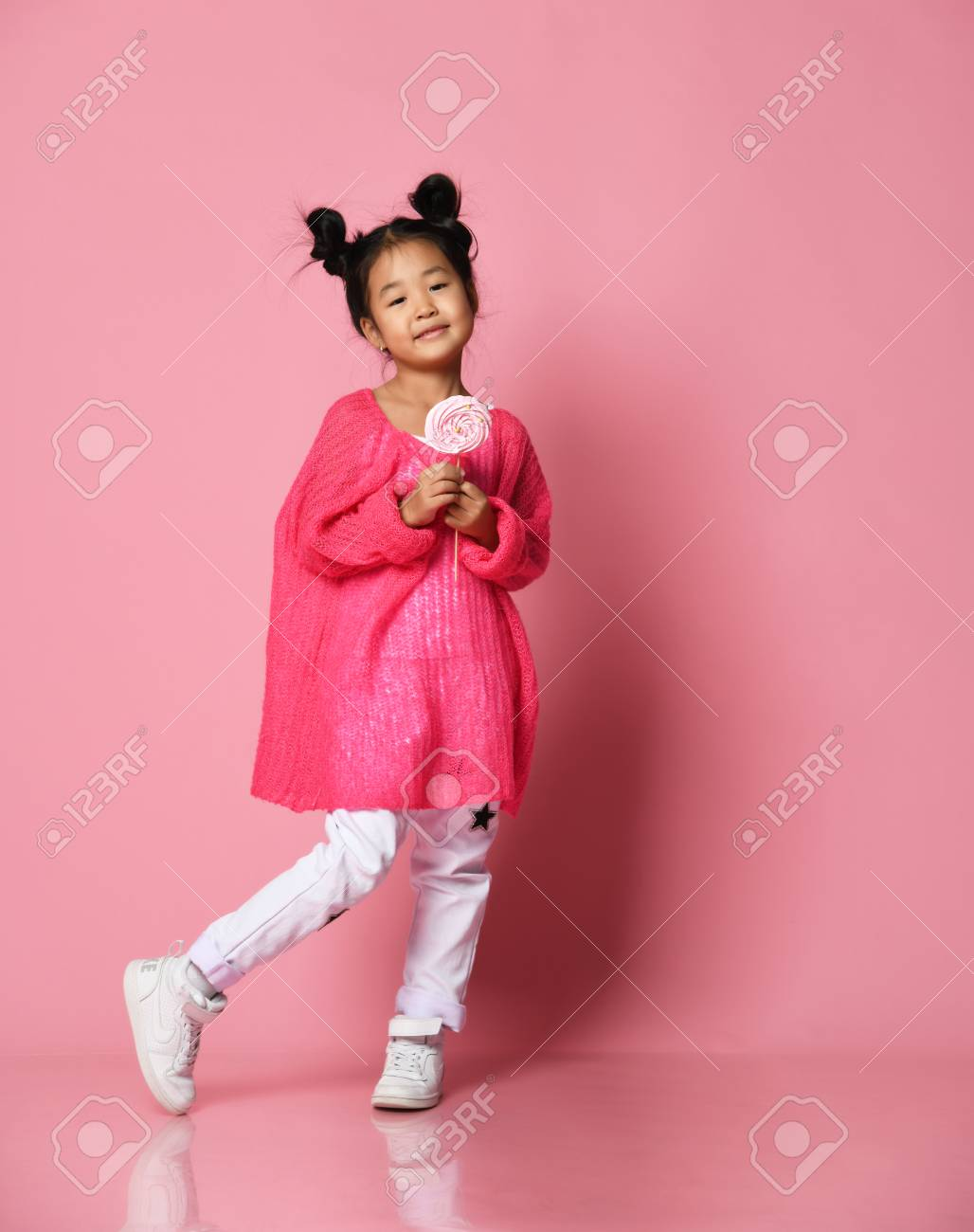 Happy young asian little girl kid lick eat happy big sweet lollypop candy on pink background - 114809662