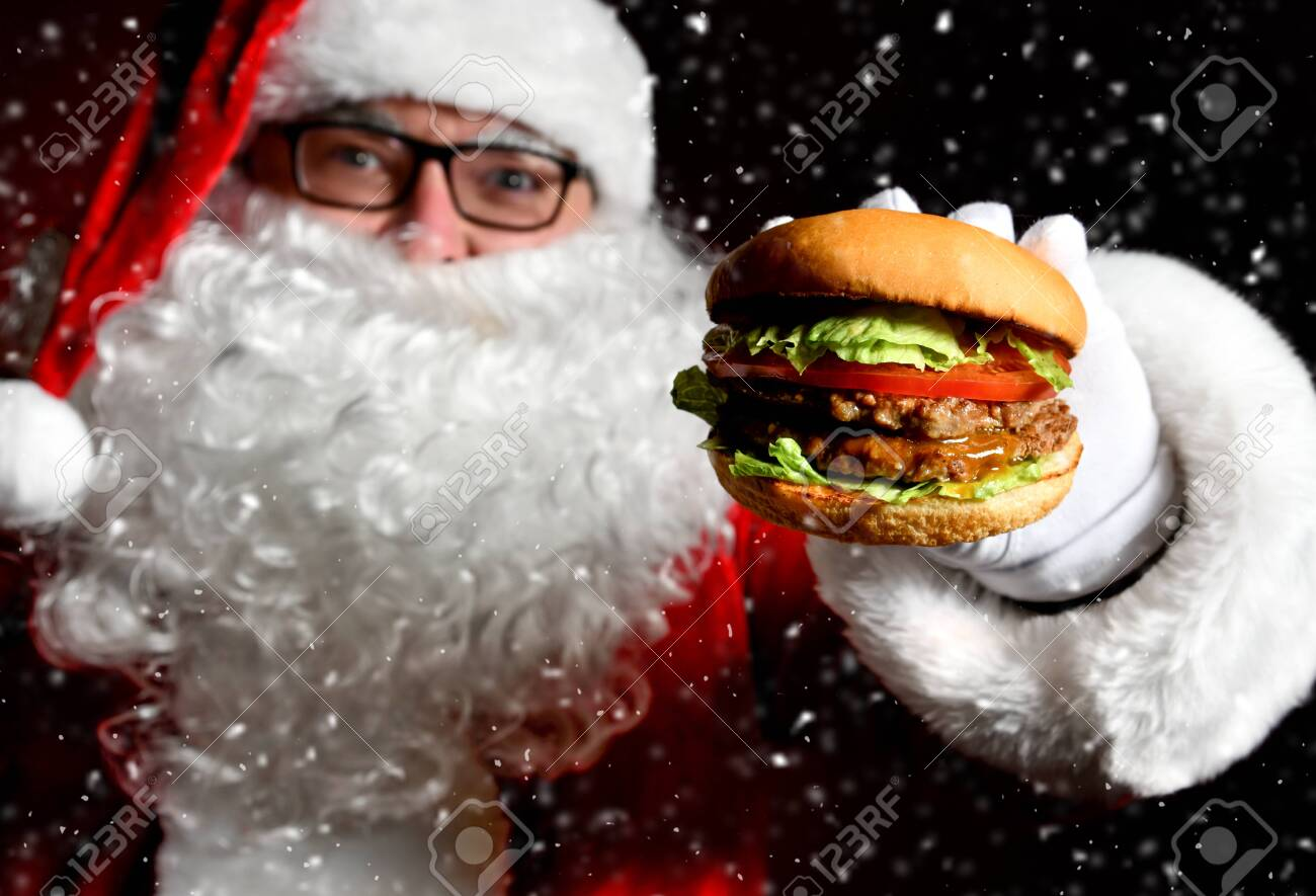 Happy Santa Claus hold tasty burger sandwich hamburger in hand closeup under snow. New year and Merry Christmas fast food concept - 135952641