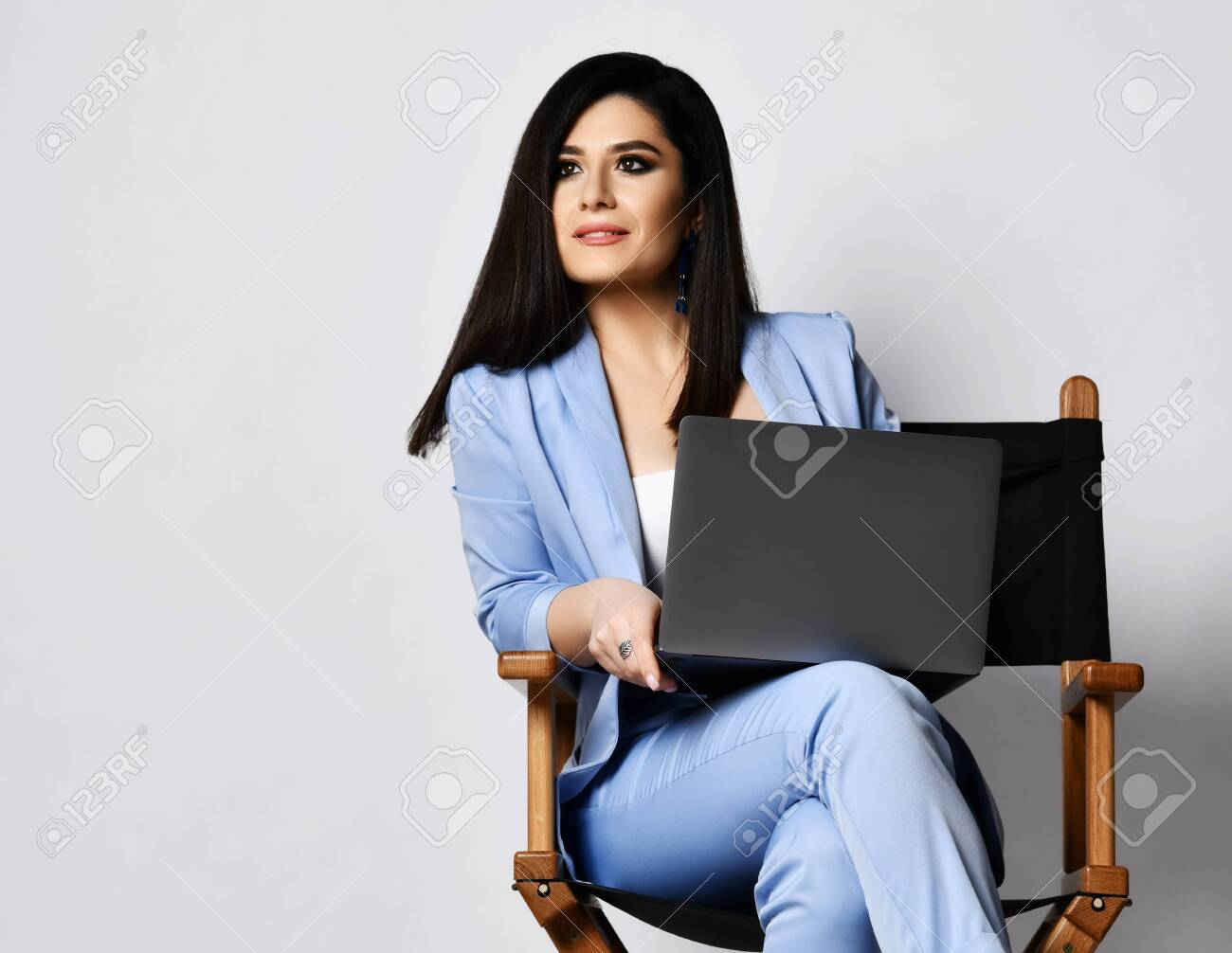 Stylish business woman in blue official pantsuit sitting with black laptop on wooden armchair and looks with interest at something on the side of her on free text copy space - 148317010