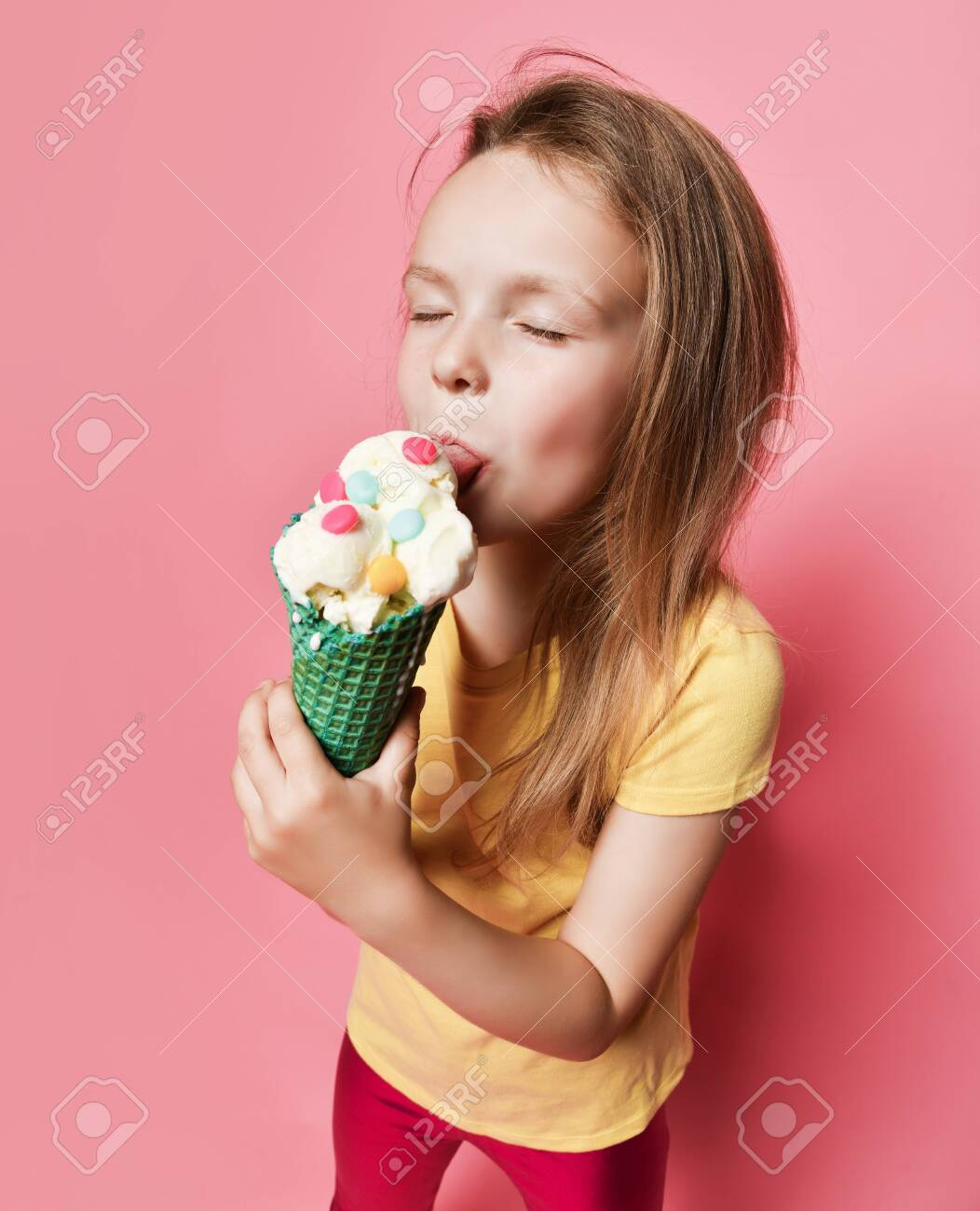 Portrait of kid girl in yellow t-shirt and pink glossy leggings relishing licking with her eyes closed eating big vanilla ice cream with candies in waffles cone. Top view - 153434884