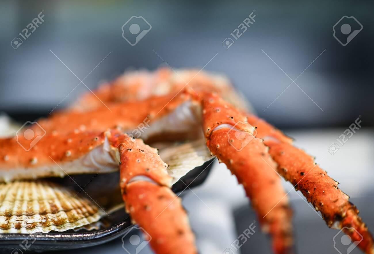 Closeup of big fresh tasty boiled crab legs on plate bowl - 154083382