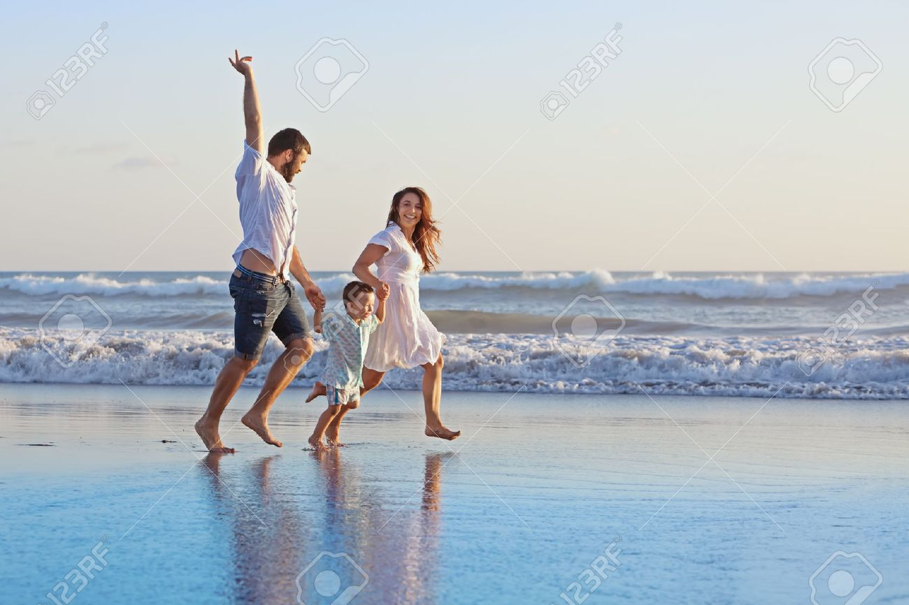 Positive family - father, mother with baby son hold hands and run  with fun along edge of sea on smooth sand beach. Active parents and people outdoor activity on tropical summer holidays with children Stock Photo - 43251792