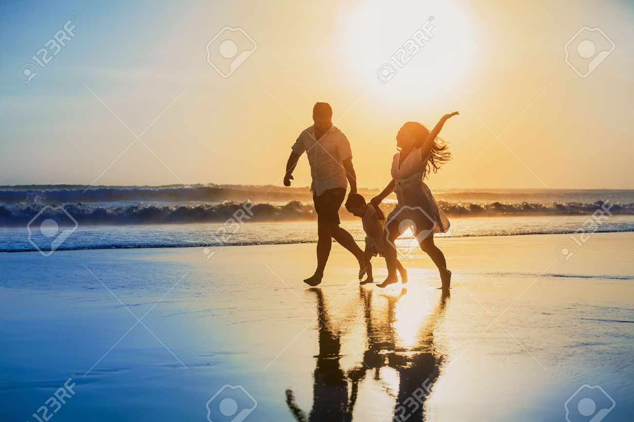Happy family - father, mother, baby son hold hands and run with fun along edge of sunset sea on black sand beach. Active parents and people outdoor activity on tropical summer vacations with children Stock Photo - 45250177