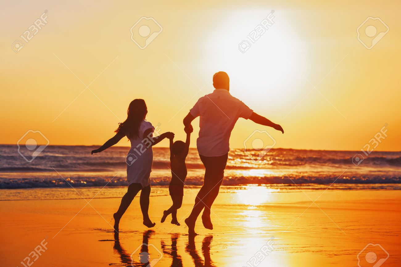 Happy family - father, mother, baby son hold hands and run with fun along edge of sunset sea on black sand beach. Active parents and people outdoor activity on tropical summer vacations with children. Stock Photo - 48039928