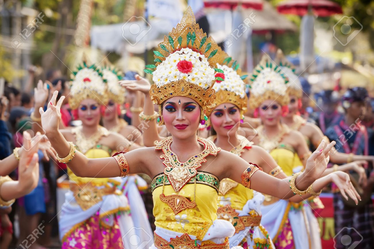 BALI, INDONESIA - JUNE 13, 2015: Beautiful women group dressed in colorful sarongs - Balinese style female dancer costume, dancing traditional temple dance Legong at Bali Art and Culture Festival show - 51412578