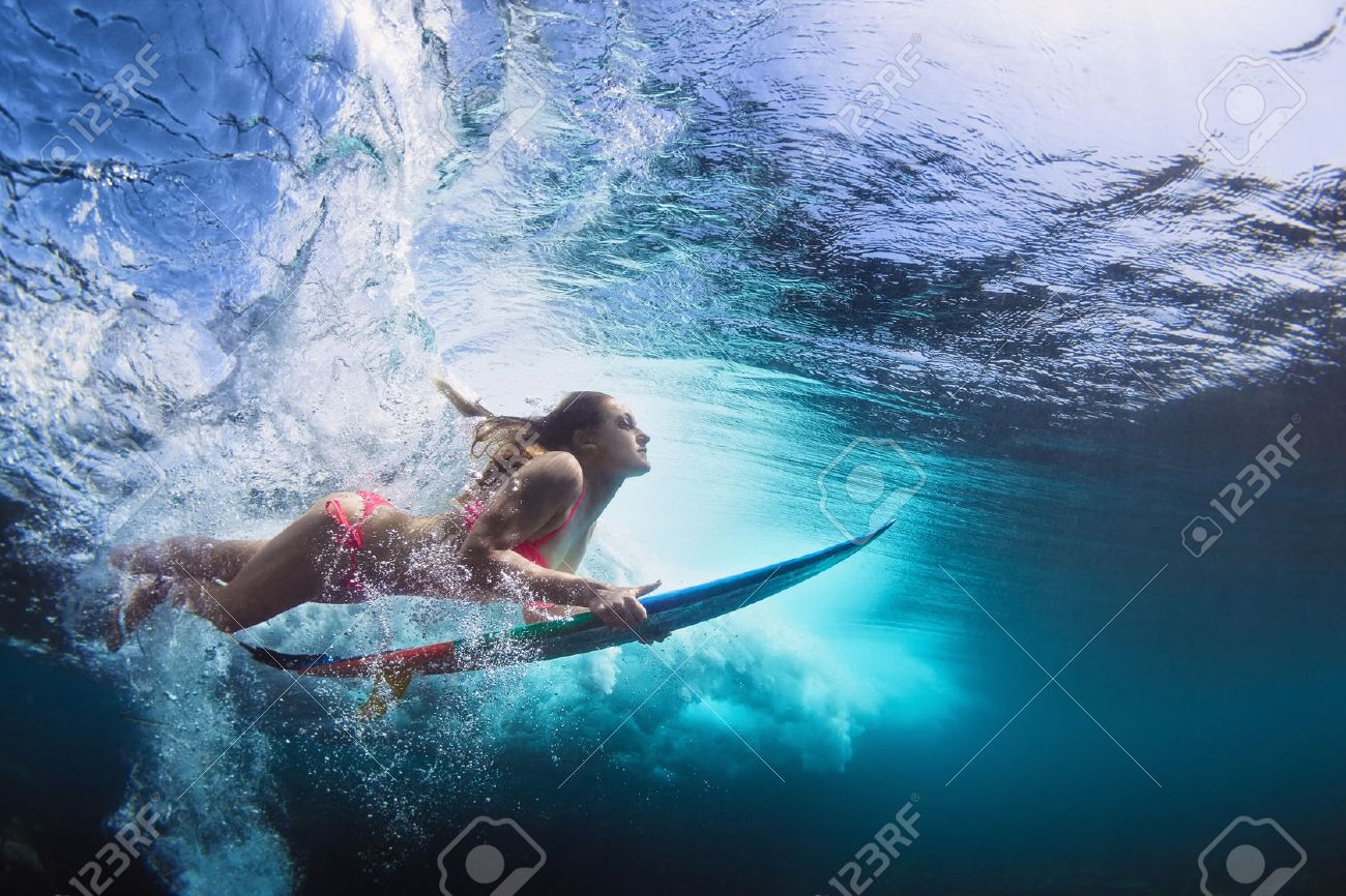 Young girl in bikini - surfer with surf board dive underwater with fun under big ocean wave. Family lifestyle, people water sport lessons and beach swimming activity on summer vacation with child - 50737128