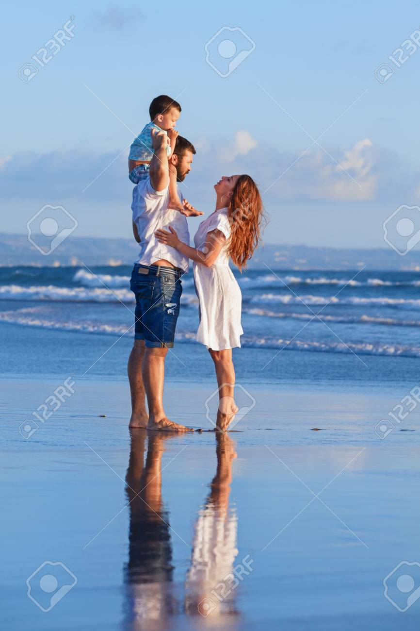 Happy full family - father, mother, baby son walk with fun along edge of sunset sea surf on black sand beach. Active parents and people outdoor activity on summer holiday with children on Bali island - 59148921