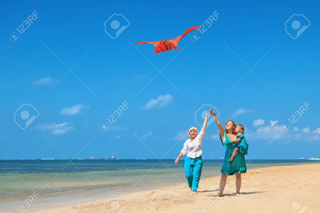 Happy family has fun on beach - grandmother, mother and baby girl walk along ocean surf. Senior woman runs with flying red kite. Active parents and people activity on summer vacation with children. - 60383760