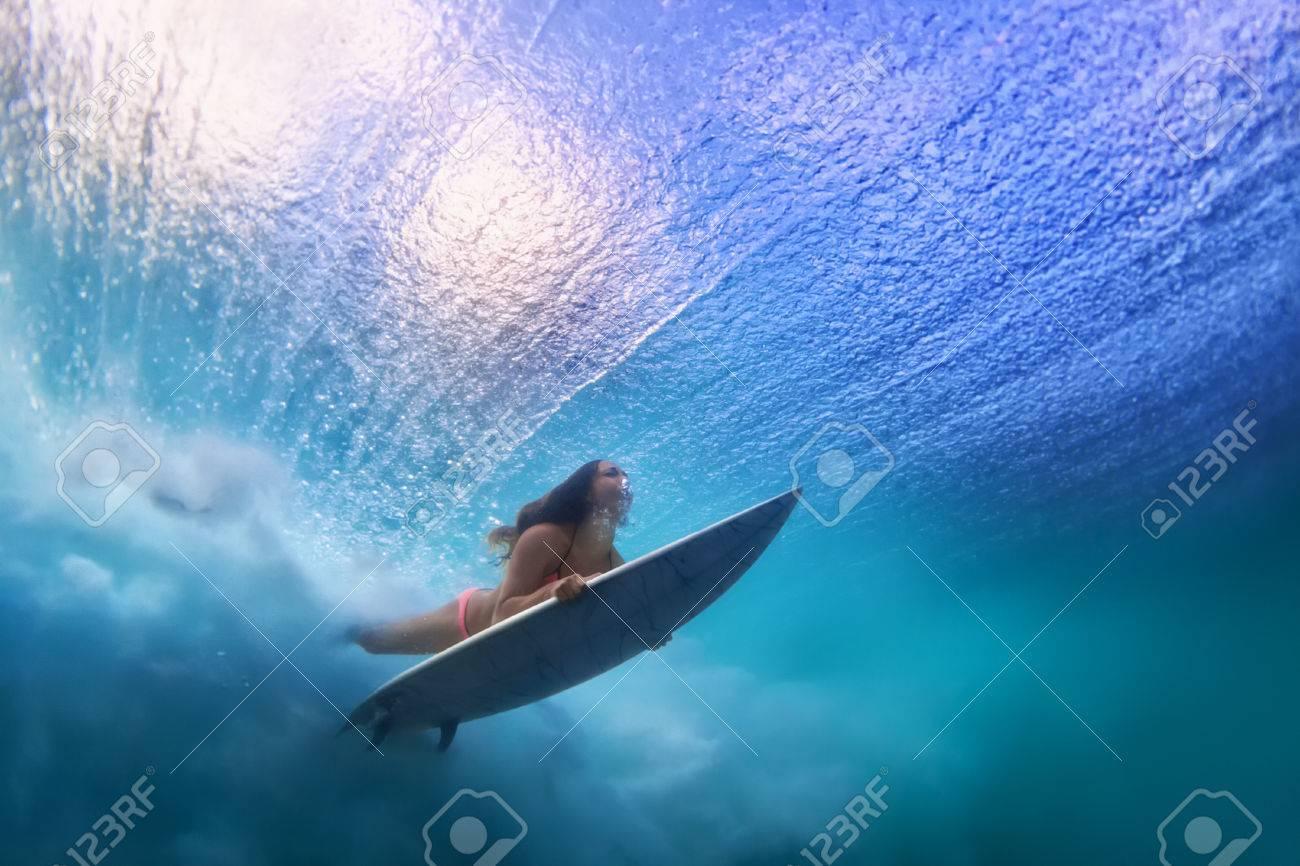 52b607a169 Sportive girl in bikini in action. Surfer with surf board dive underwater  under breaking ocean