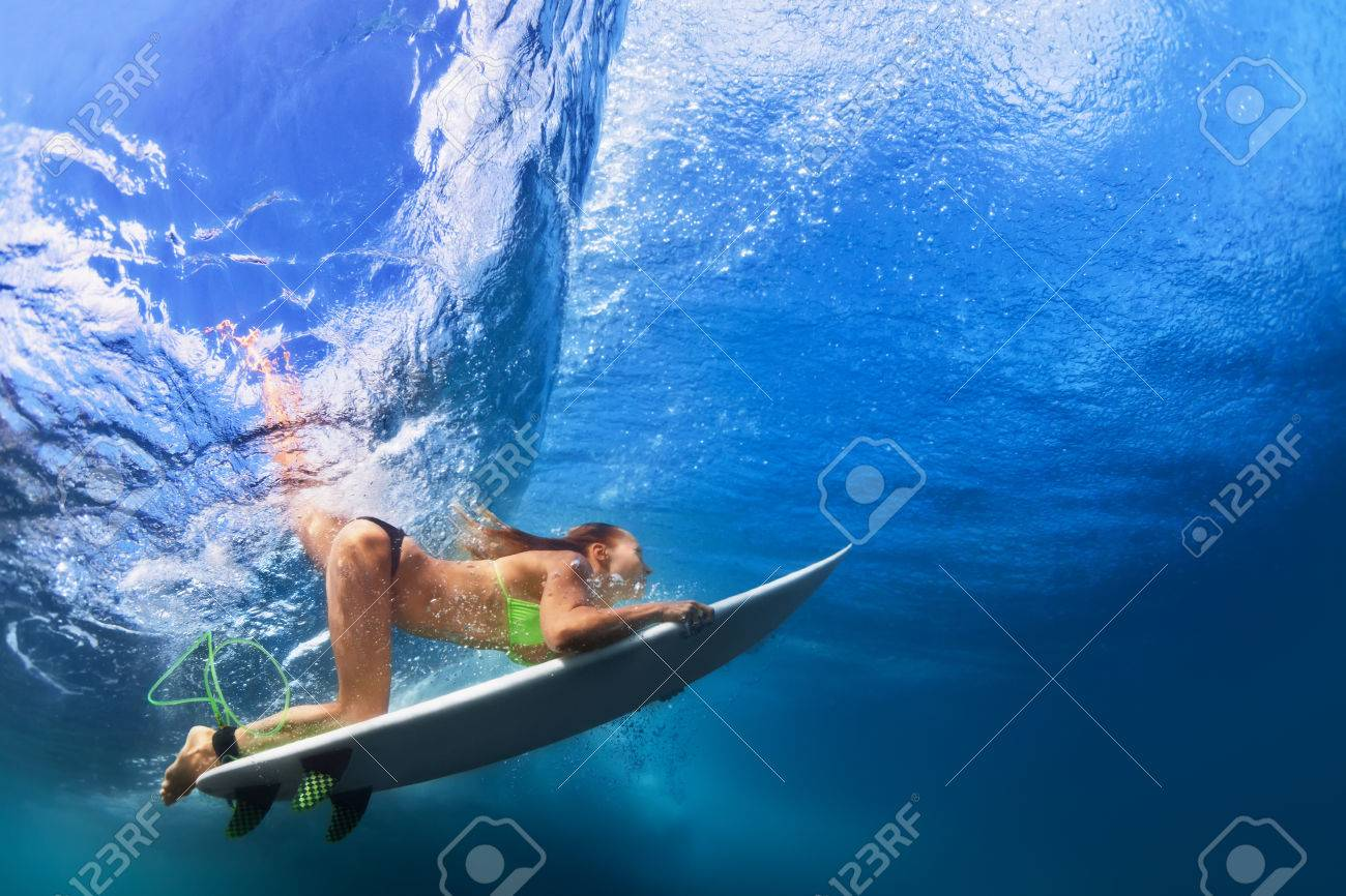 50a57a8271 Active girl in bikini in action. Surfer woman with surf board dive  underwater under breaking