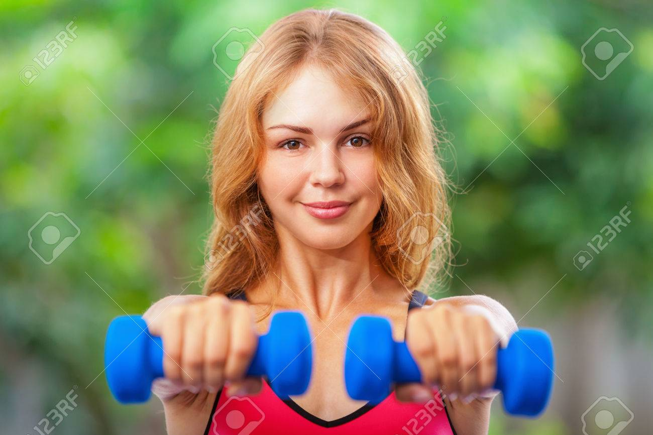 Active sporty woman doing morning exercises with dumbbells at