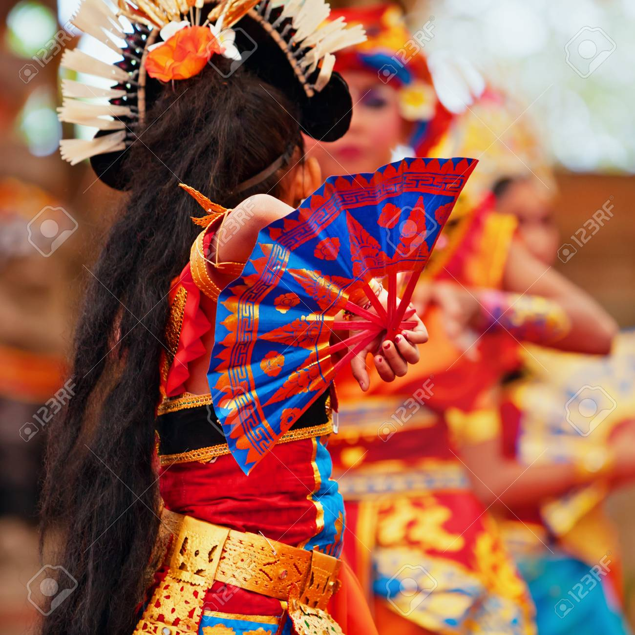 Asian travel background. Group of beautiful Balinese dancer women in  traditional Sarong costumes with fans