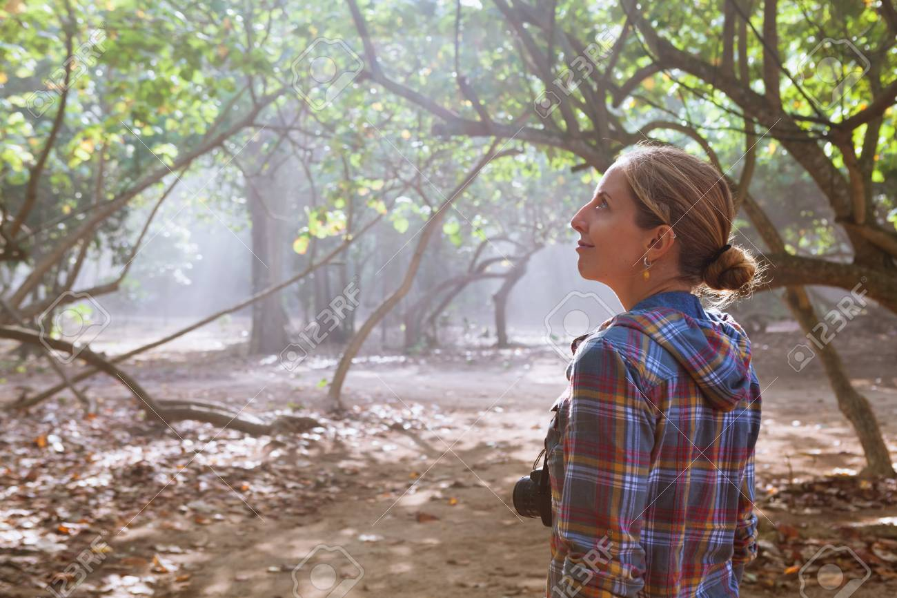 In the misty morning happy girl with photo camera walk alone by jungle path, explore tropical rain forest. Family travel lifestyle, outdoor hiking activity. Summer vacation with kid on tropical island - 106551301