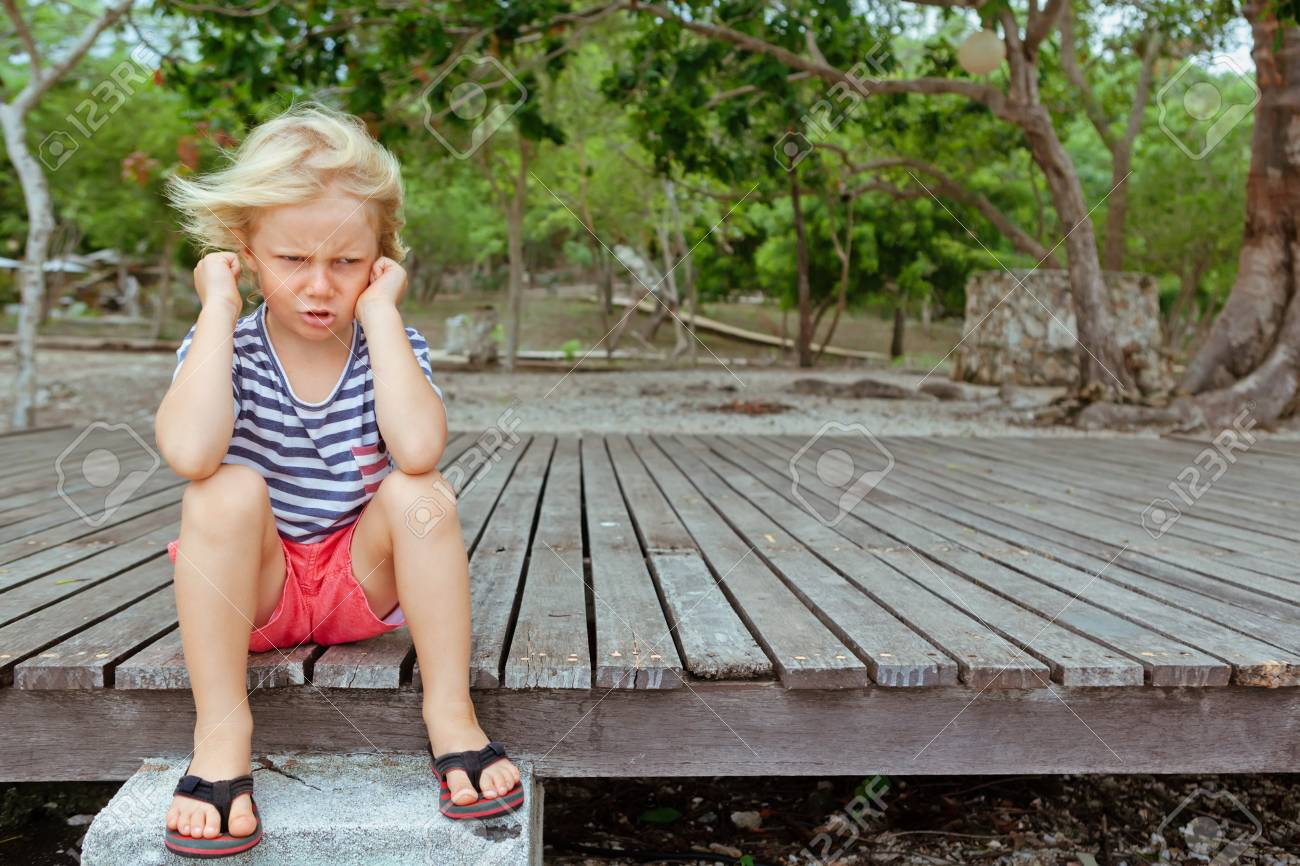 Funny portrait of caucasian kid looking annoyed and unhappy. Upset and angry child concept for family relations, social problems issues and juvenile psychology. Outdoor background with copy space. - 119819770