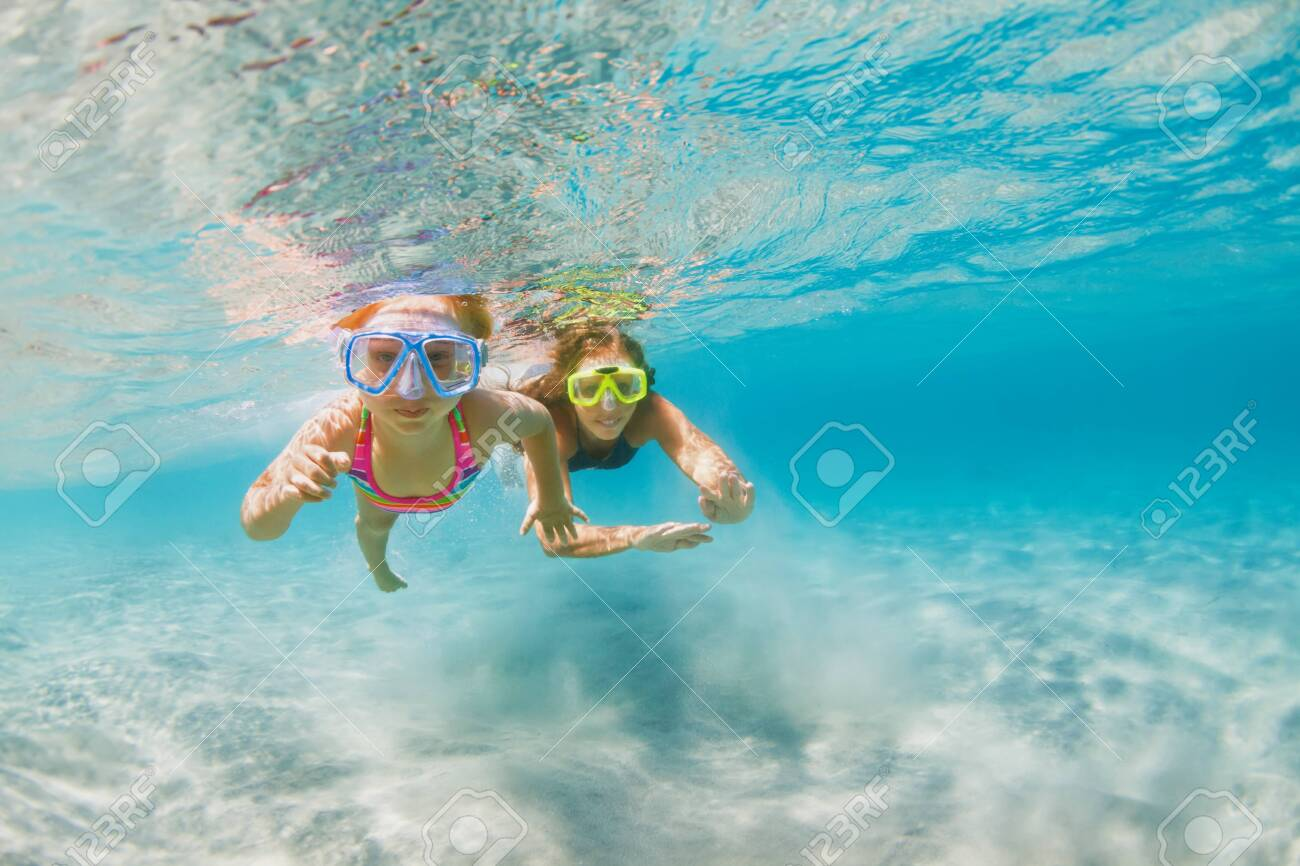 Young mother with child in snorkeling mask dive in coral reef sea lagoon to explore underwater world. - 156563668