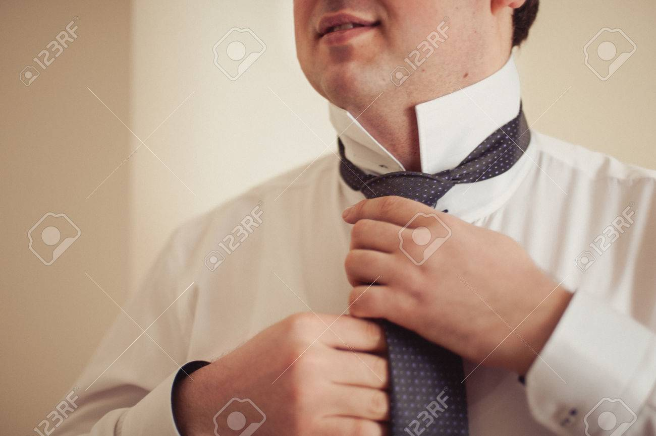 The groom puts on his tie a business man is dressing a tie stock the groom puts on his tie a business man is dressing a tie stock ccuart Choice Image