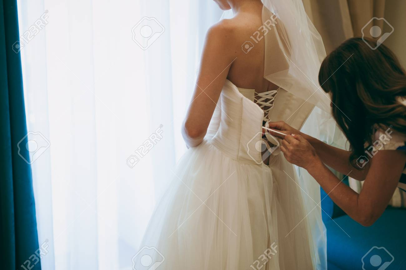 eee11fcd5160 Fashionable bridesmaids dresses helped wear bow on back of wedding dress  bride. Morning wedding day