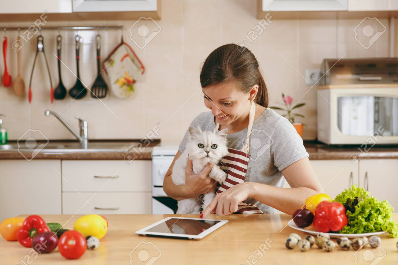 The Young Pretty Woman With White Persian Cat In The Kitchen