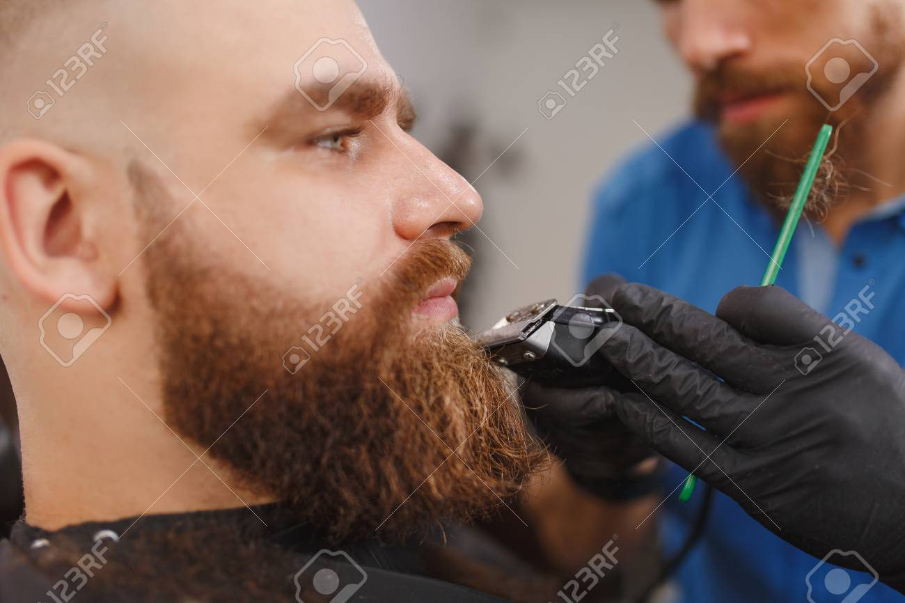 Close Up Of Male Professional Hairdresser Serving Client With Thick Big Beard By Clipper Ginger Handsome Brutal Stylish Young Man Getting Trendy Haircut In